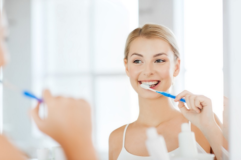 Woman brushing her porcelain veneers from Aesthetic Dental Studio